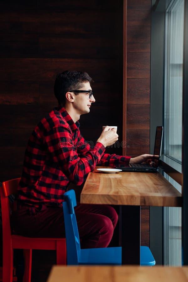 O homem de negócios novo aprecia o café no café que fala no telefone e que usa um portátil fotografia de stock