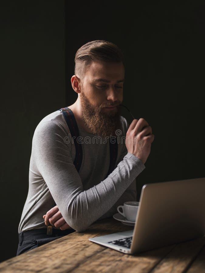 O homem de negócios novo atrativo está usando um computador fotografia de stock
