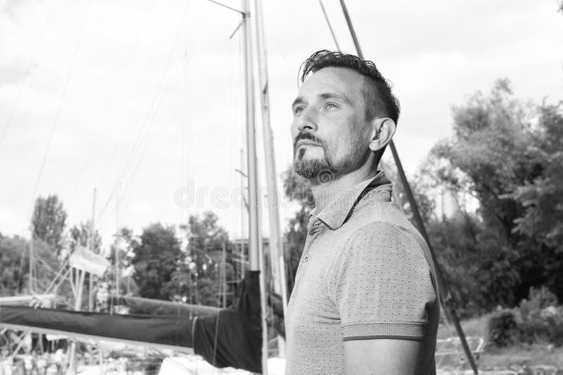 O homem de negócios novo bem sucedido está apreciando o tempo livre no porto Retrato dos 'yachtsman's com barco fotografia de stock