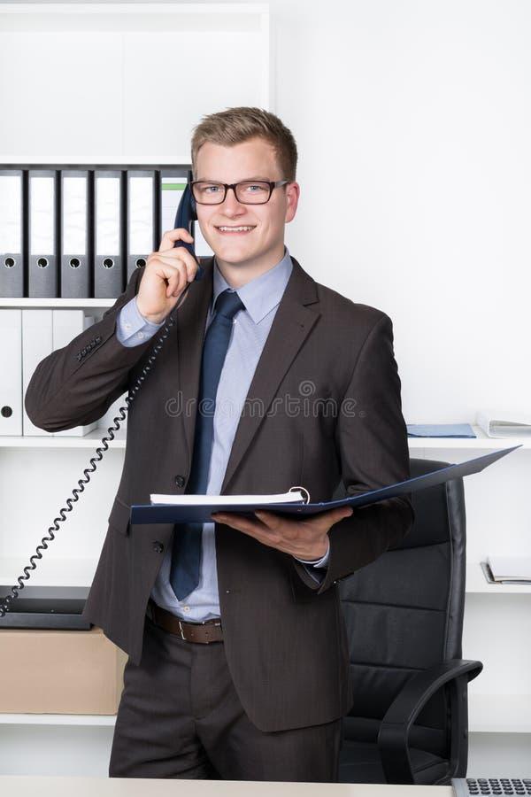 O homem de negócios novo com arquivo está telefonando no escritório fotografia de stock