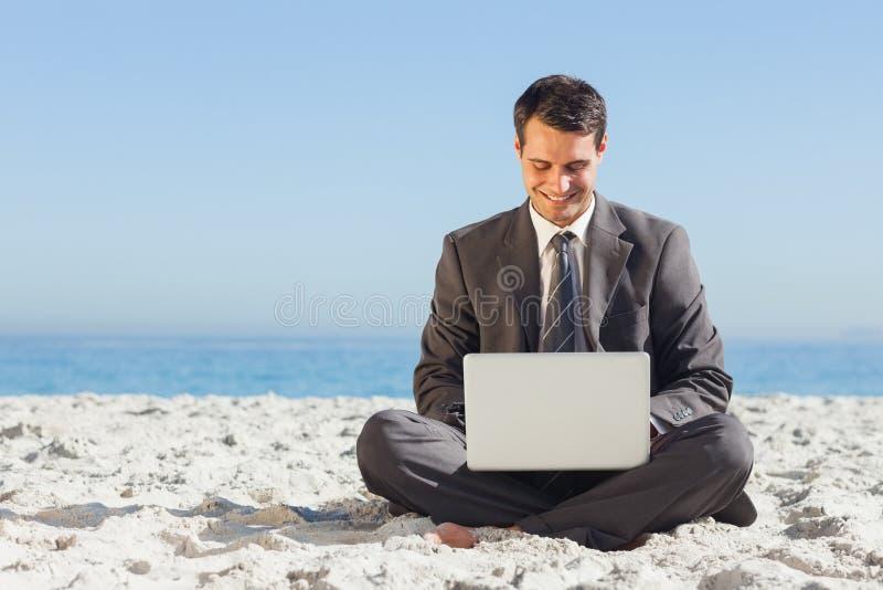 O homem de negócios novo com pés cruzou a datilografia em seu portátil fotos de stock royalty free
