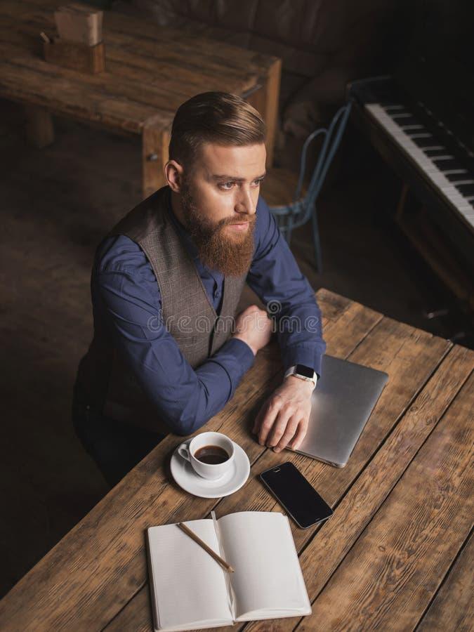 O homem de negócios novo considerável está descansando no café imagem de stock