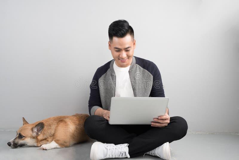 O homem de negócios novo considerável está usando o portátil ao sentar-se com olá! fotos de stock