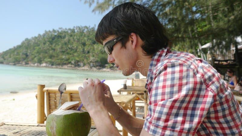 O homem de negócios novo considerável nos óculos de sol bebe o suco fresco do coco em um café da praia com opinião do mar em palm fotografia de stock royalty free