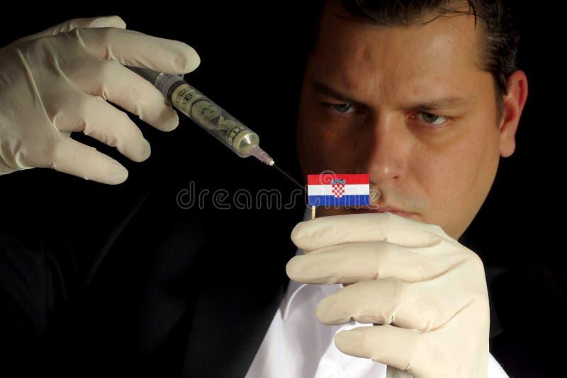 O homem de negócios novo dá-me a uma injeção financeira à bandeira croata foto de stock