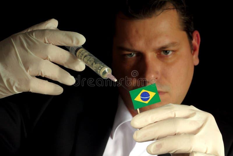 O homem de negócios novo dá uma injeção financeira à bandeira brasileira fotos de stock royalty free