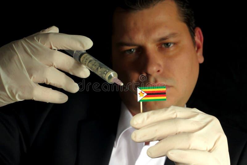 O homem de negócios novo dá uma injeção financeira à bandeira zimbabuense imagem de stock