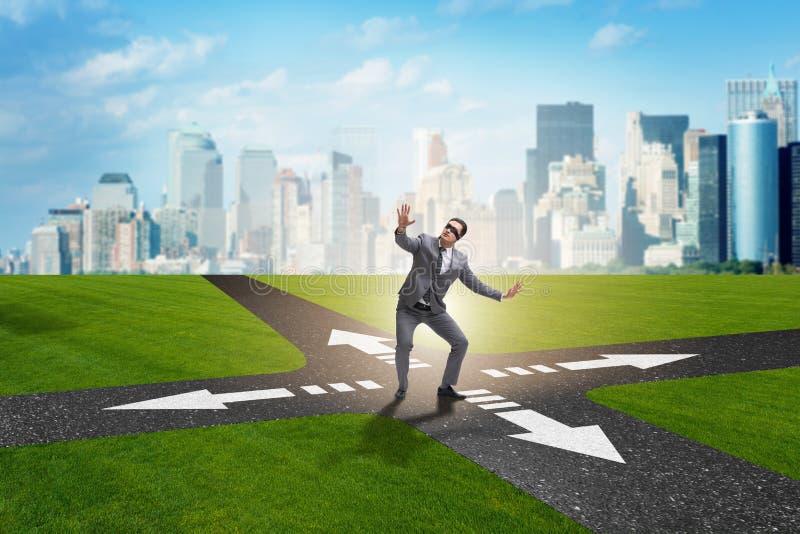 O homem de negócios novo em estradas transversaas no conceito da incerteza imagens de stock