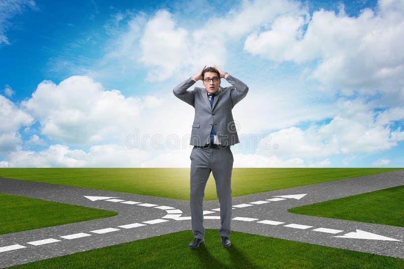 O homem de negócios novo em estradas transversaas no conceito da incerteza imagens de stock royalty free