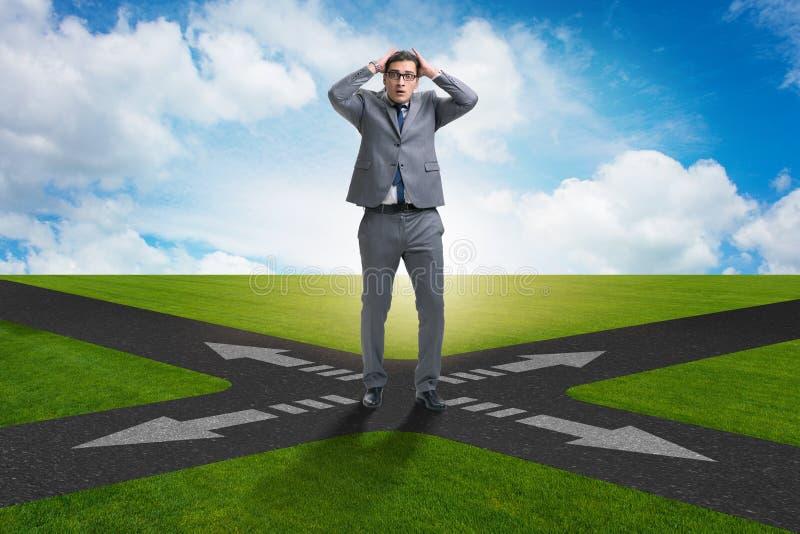 O homem de negócios novo em estradas transversaas no conceito da incerteza fotos de stock