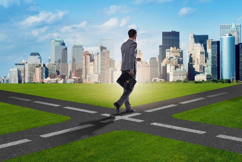 O homem de negócios novo em estradas transversaas no conceito da incerteza fotografia de stock