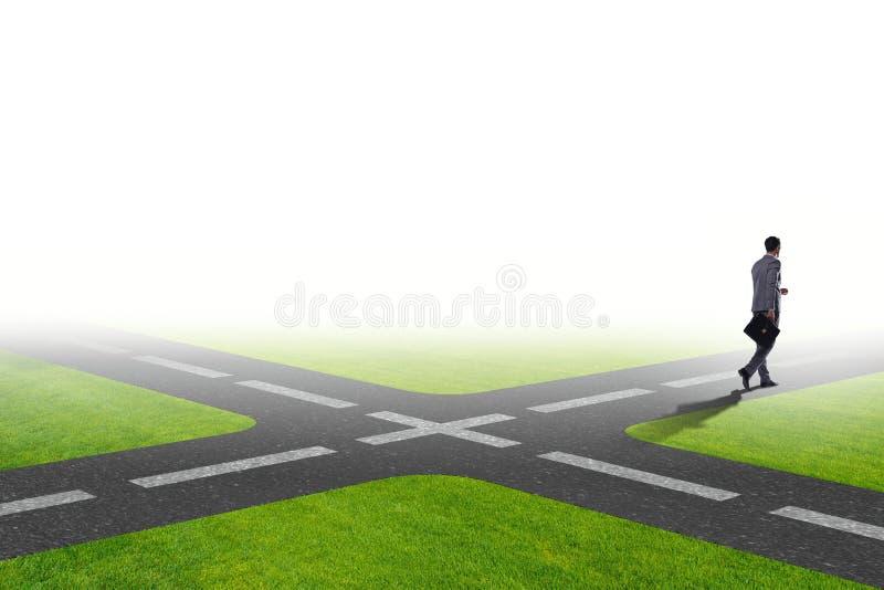 O homem de negócios novo em estradas transversaas no conceito da incerteza imagem de stock royalty free