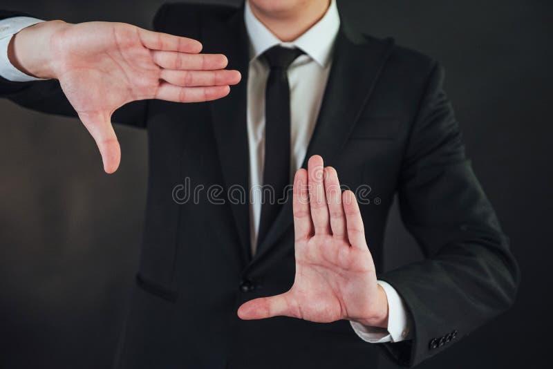 O homem de negócios novo em um terno mostra sua mão em um fundo escuro imagens de stock royalty free