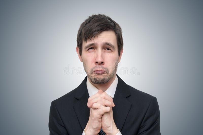 O homem de negócios novo engraçado é de pedido ou pedindo a ajuda imagens de stock