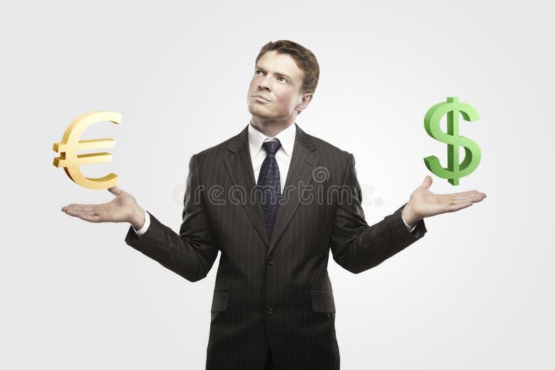 O homem de negócios novo escolhe sinais do euro ou de dólar. fotos de stock royalty free