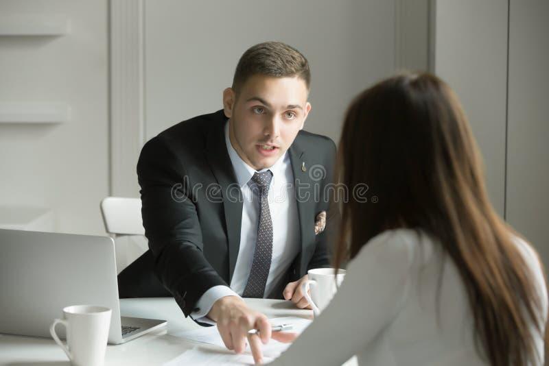 O homem de negócios novo está apontando a um erro em um papel foto de stock