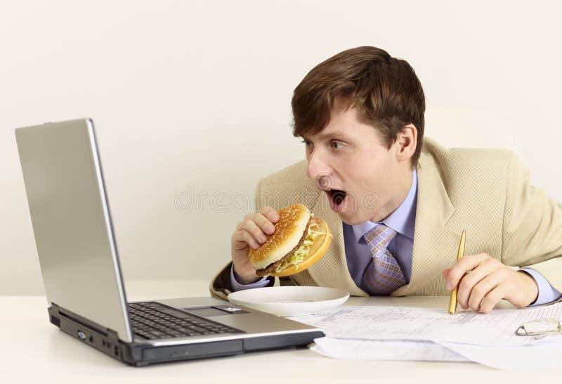 O homem de negócios novo está indo comer o sanduíche fotografia de stock