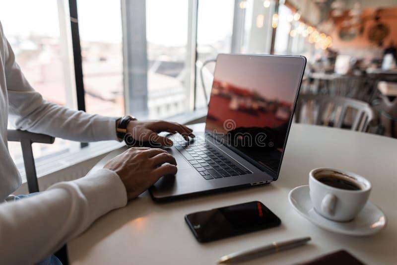 O homem de negócios novo está sentando-se em uma tabela em um café e em um texto de datilografia em um computador moderno Portáti fotos de stock