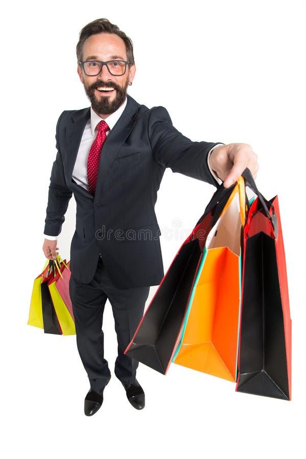 O homem de negócios novo farpado fez a compra e a terra arrendada coloriu sacos de papel no conceito da oportunidade da venda e d foto de stock royalty free