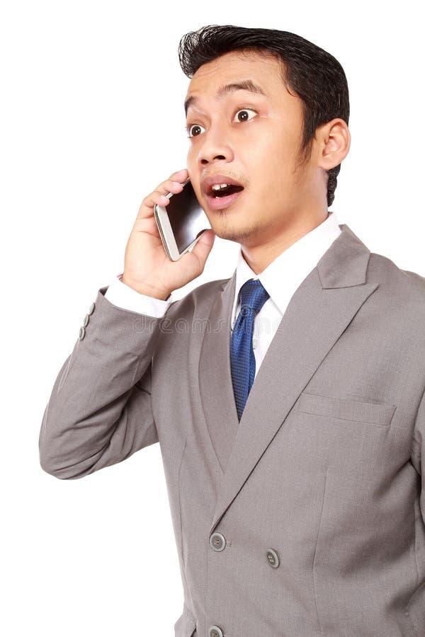 O homem de negócios novo foi surpreendido receber um telefone imagem de stock