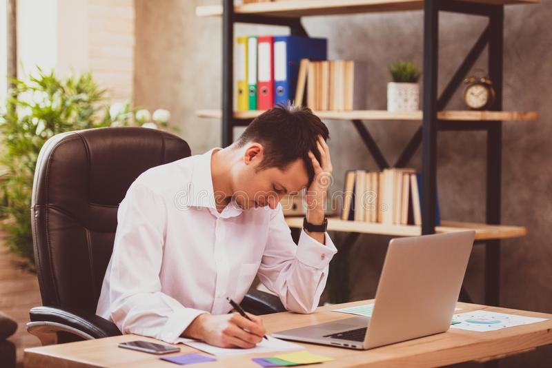 O homem de negócios novo forçado chocado por más notícias usando o portátil no trabalho, acionista falido desesperado perdeu o di foto de stock royalty free