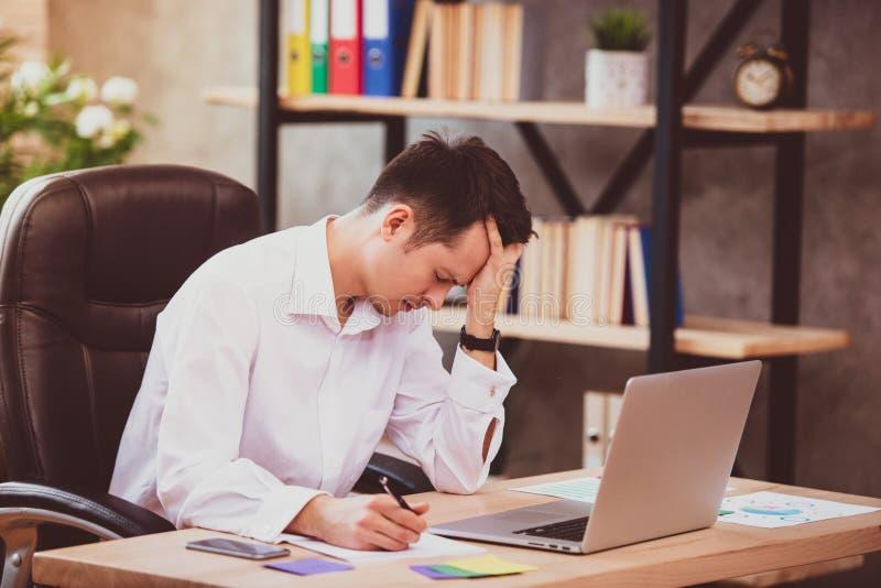 O homem de negócios novo forçado chocado por más notícias usando o portátil no trabalho, acionista falido desesperado perdeu o di fotos de stock