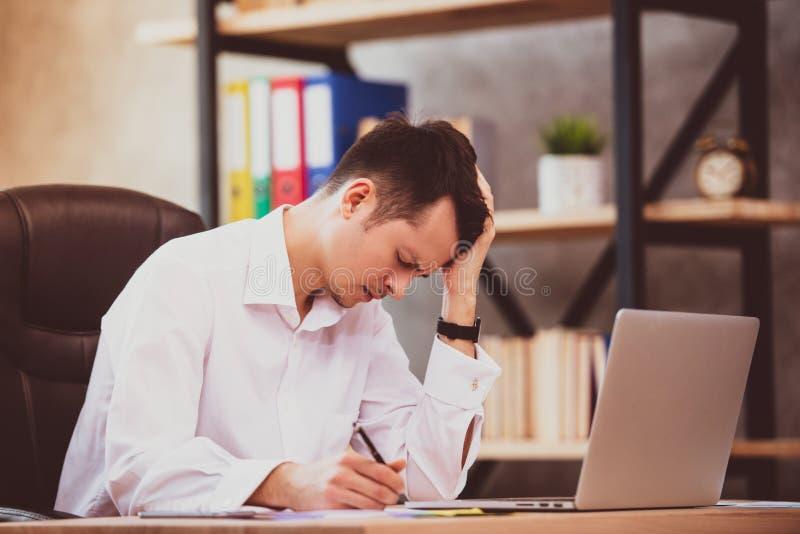 O homem de negócios novo forçado chocado por más notícias usando o portátil no trabalho, acionista falido desesperado perdeu o di fotos de stock royalty free