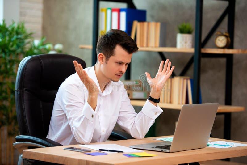 O homem de negócios novo forçado chocado por más notícias usando o portátil no trabalho, acionista falido desesperado perdeu o di imagens de stock