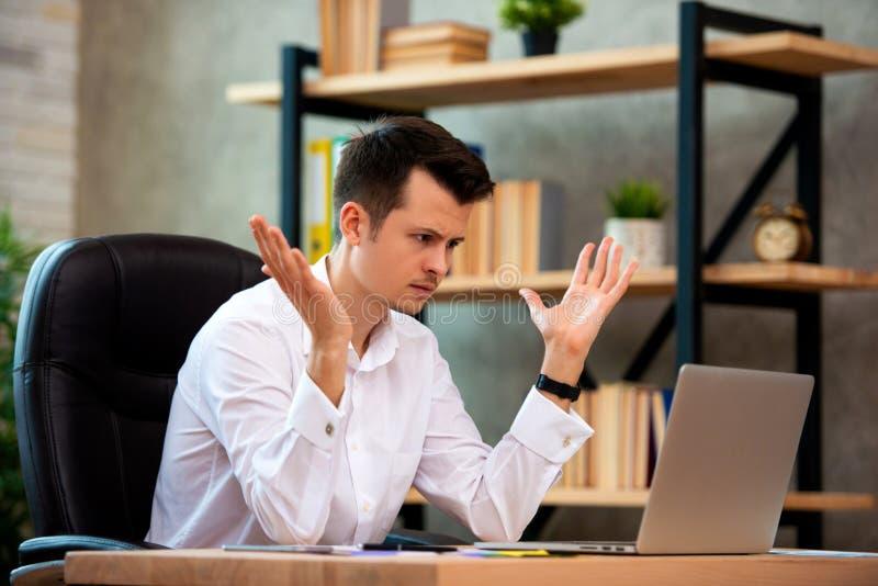 O homem de negócios novo forçado chocado por más notícias usando o portátil no trabalho, acionista falido desesperado perdeu o di foto de stock