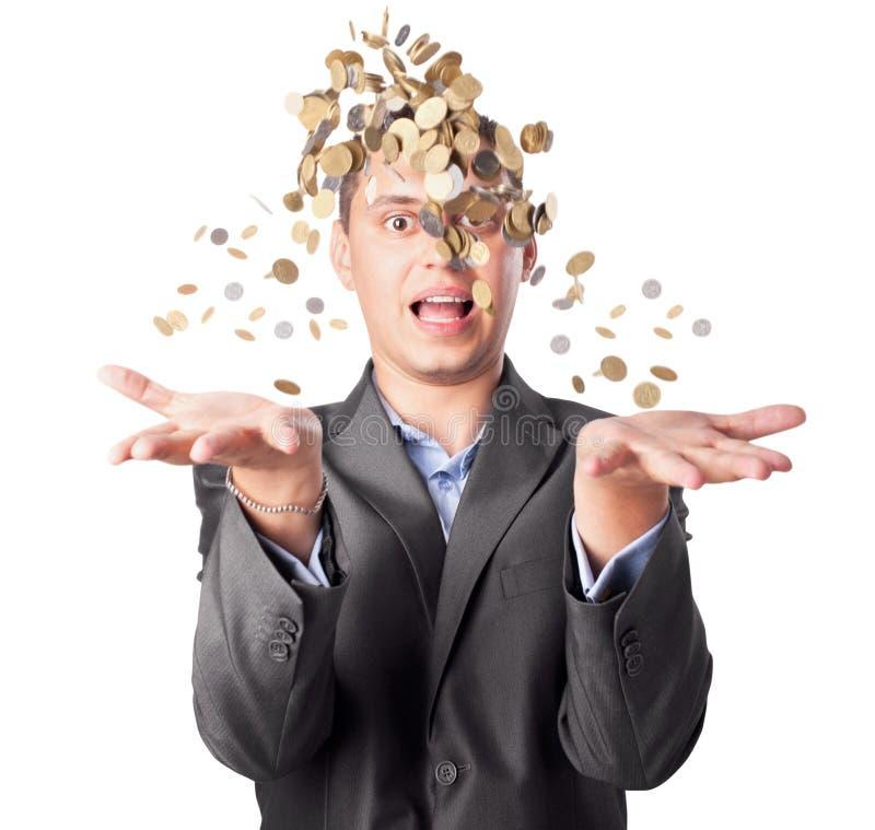 O homem de negócios novo joga acima muitas moedas imagem de stock