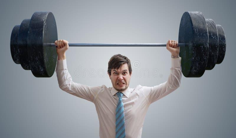 O homem de negócios novo na camisa está levantando pesos pesados fotografia de stock