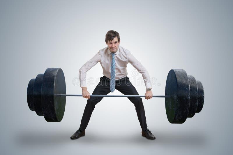 O homem de negócios novo na camisa está levantando pesos pesados fotos de stock
