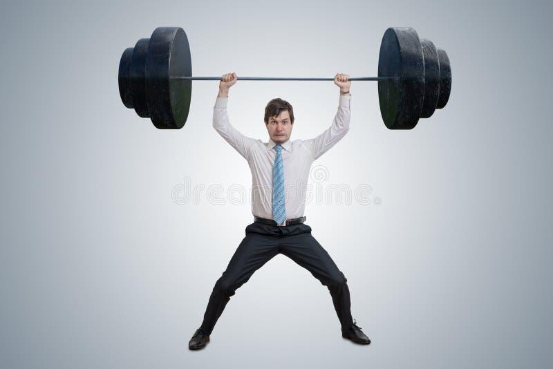 O homem de negócios novo na camisa está levantando pesos pesados imagens de stock royalty free