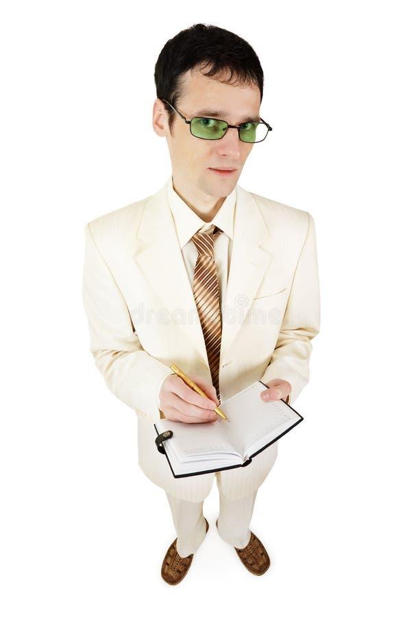O homem de negócios novo no terno claro escreve no caderno imagem de stock