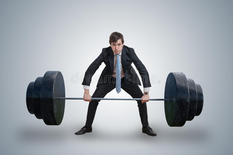 O homem de negócios novo no terno está levantando pesos pesados fotos de stock royalty free