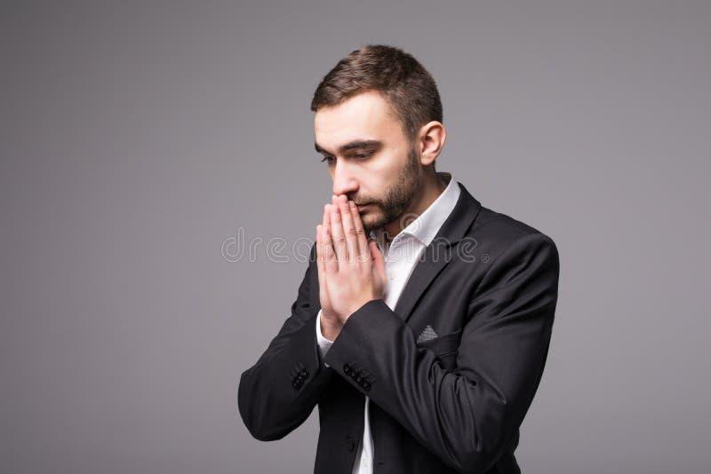 O homem de negócios novo no terno reza imagem de stock