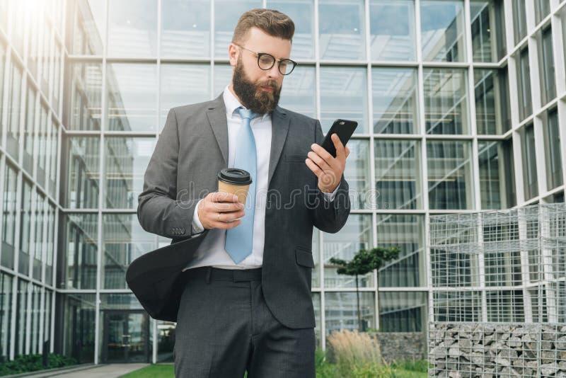 O homem de negócios novo nos monóculos, no terno e no laço está estando exterior, está usando o smartphone e está bebendo o café imagem de stock royalty free