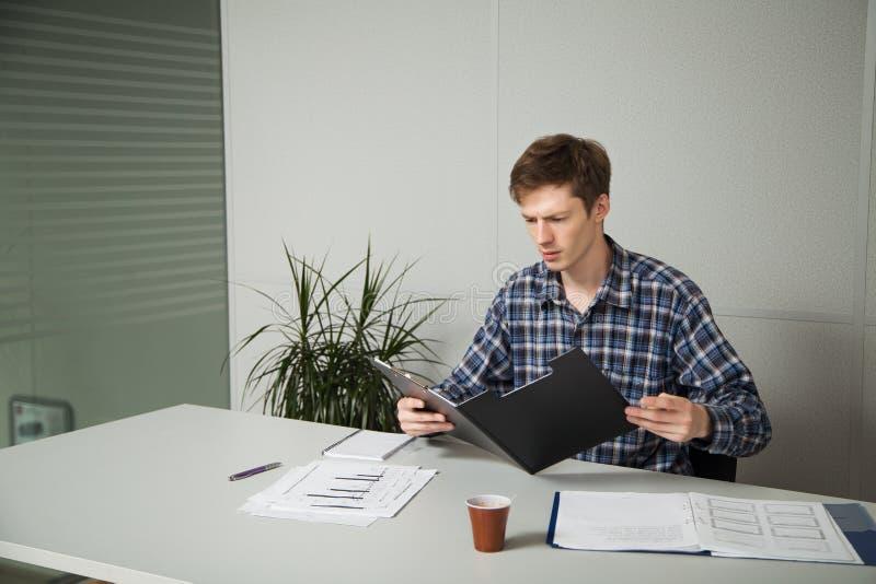 O homem de negócios novo olha de sobrancelhas franzidas, lendo a notícia no relatório, sentando-se em uma mesa no local de trabal foto de stock royalty free