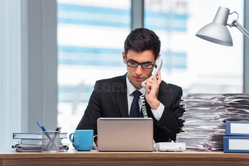 O homem de negócios novo que fala no telefone foto de stock