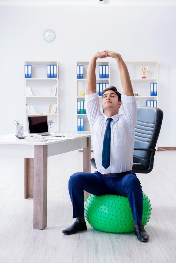 O homem de negócios novo que faz os esportes que esticam no local de trabalho imagens de stock royalty free