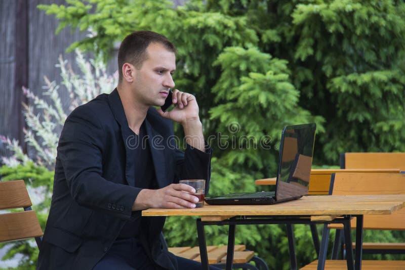 O homem de negócios novo seguro vestiu-se no revestimento que fala no telefone celular ao sentar-se com laptop fora foto de stock royalty free
