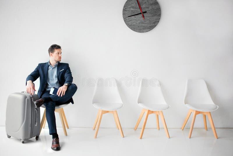 O homem de negócios novo senta-se na sala de espera Guarda um pé em outro e olha para endireitar O homem tem a mão na mala de via imagens de stock