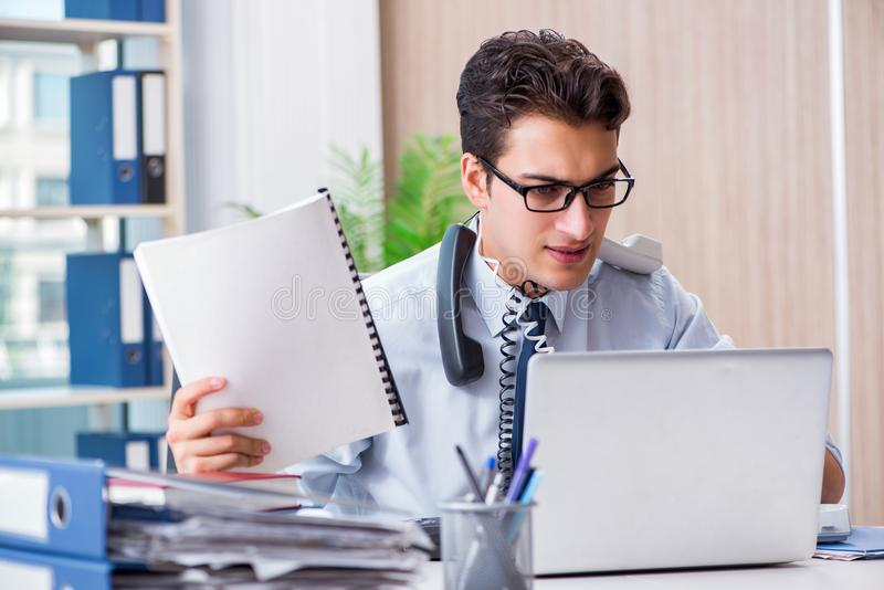 O homem de negócios novo sob a pressão no escritório entregar tarefas fotografia de stock royalty free