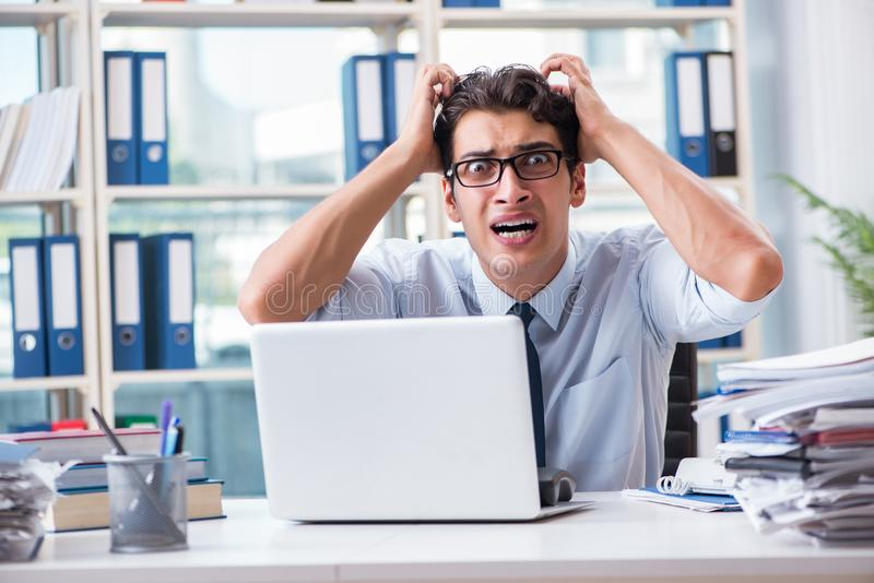 O homem de negócios novo sob a pressão no escritório entregar tarefas imagens de stock