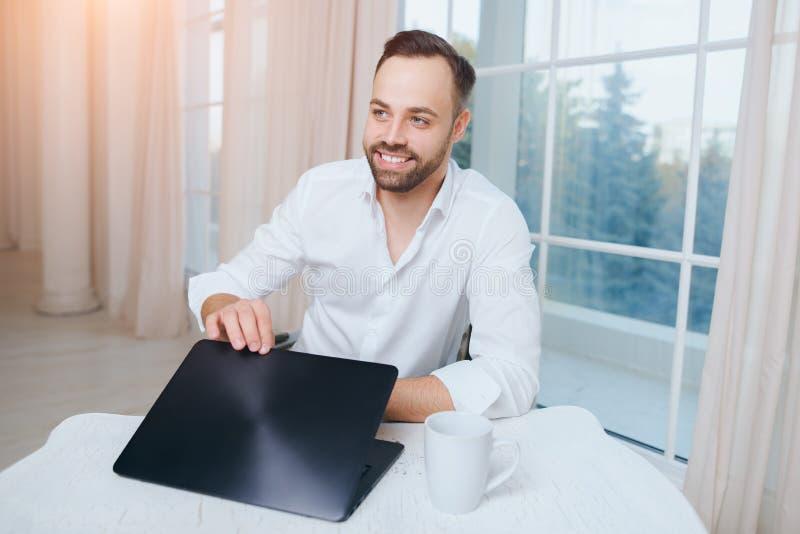 O homem de negócios novo de sorriso, abre um portátil para o trabalho imagem de stock