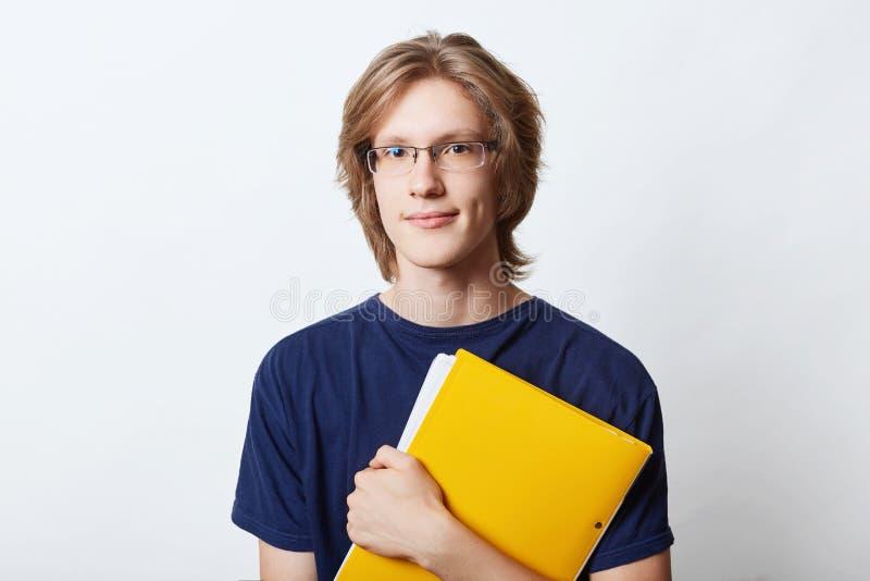O homem de negócios novo vestiu-se ocasionalmente, eyewear vestindo, tendo o penteado à moda, mantendo-se no dobrador amarelo das fotografia de stock