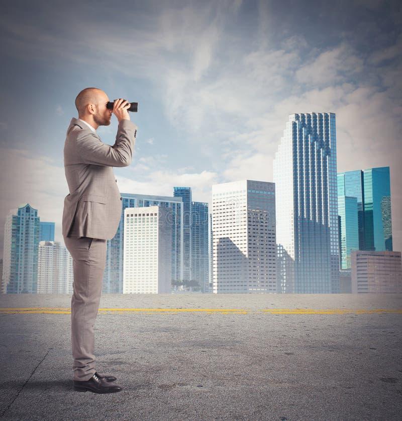 O homem de negócios observa de uma distância fotos de stock
