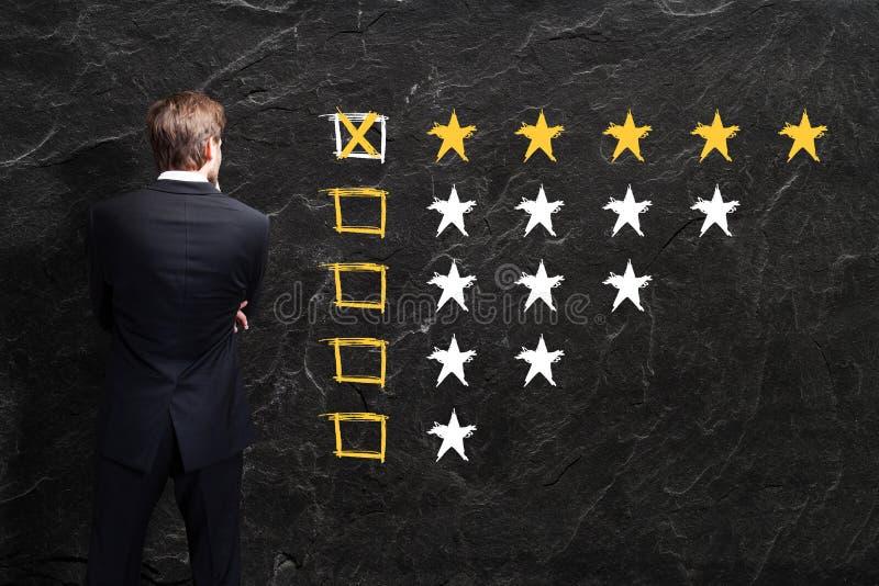 O homem de negócios olha uma avaliação de cinco estrelas fotografia de stock