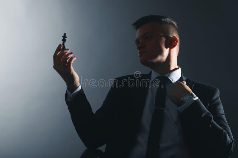 O homem de negócios olha uma parte de xadrez Silhueta do líder imagem de stock royalty free