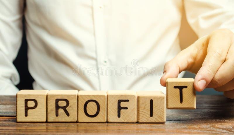 O homem de negócios põe blocos de madeira com o lucro da palavra O resultado financeiro da empresa por um determinado período de  foto de stock